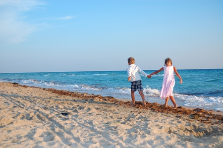 along: two kids walking along the beach together Stock Photo