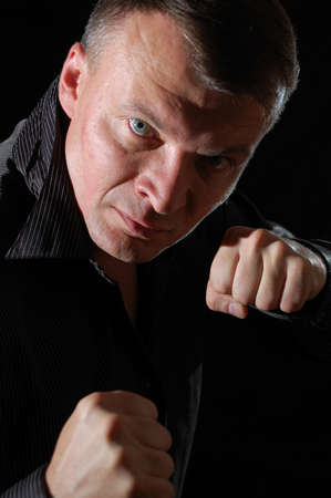 close-up studio portrait of a middle-aged angry man ready for boxing photo