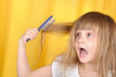 naughty girl: little girl trying to brush her hair with a hairbrush
