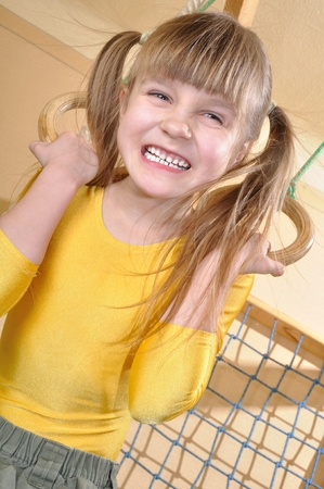 6 year old girl  playing with her home wooden gym  photo