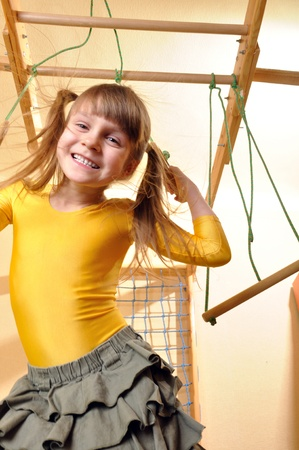 6 year old girl  playing at her home wooden gym photo