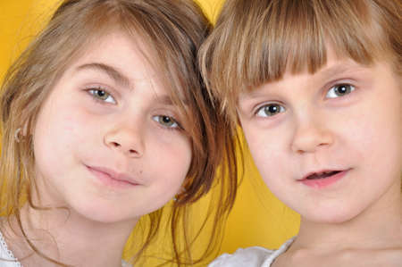 portrait of two 6 year old friends against yellow photo