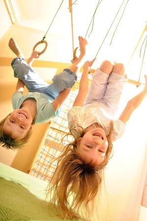 trois enfants: deux enfants hanging jouant sur des anneaux gymnastique Banque d'images