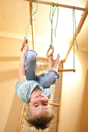 happy smiling 6 year old boy hanging on gymnastic rings photo