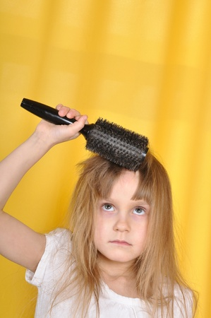 little girl trying to brush her hair with a hairbrush photo