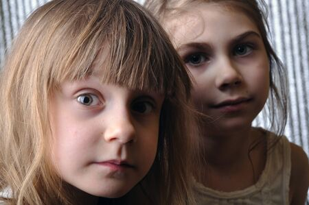 beautiful sad: close-up portrait of two serious girls  Stock Photo