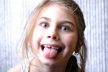 naughty or nice: close-up portrait of a cheerful girl with her tongue out Stock Photo