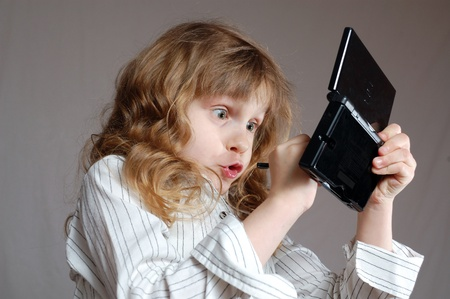 games hand: child playing a video game on a mini computer with double screens Stock Photo