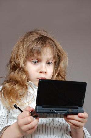 child playing a video game on a mini computer with double screens Stock Photo - 9619032