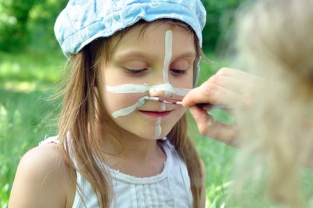 outdoor portrait of a child with her face being painted  photo