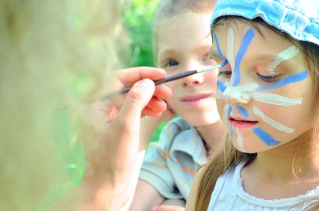 outdoor portrait of a child with his face being painted