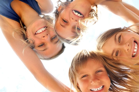 embracement: Group of happy smiling girls playing together. From below view. Stock Photo