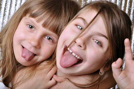 thier: two playful girls with thier tongues out