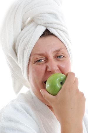 woman in bath: adult woman in a white bathrobe and towel on her head biting an apple