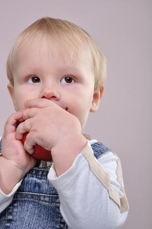 retrato de un niño de 1 año de edad morder una manzana Foto de archivo