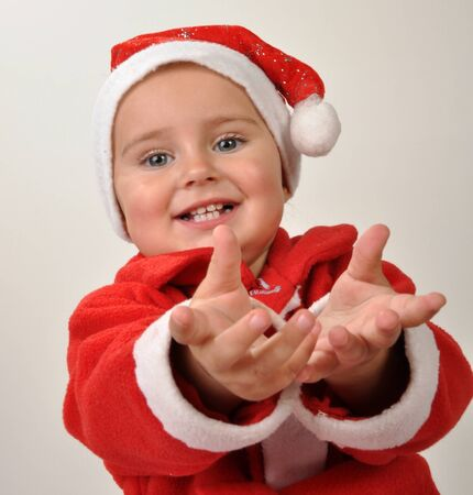 little  girl wearing a Santa Clause hat giving or asking for Christmas presebt photo