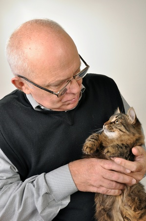 senior man wearing glasses with a cat photo