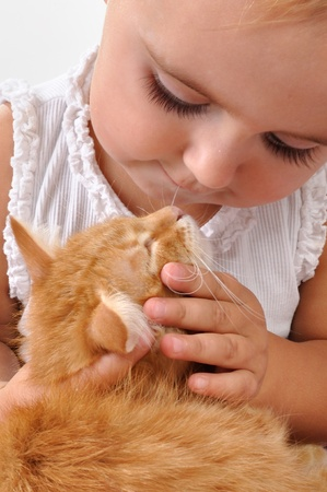 young child playing with a red kitten