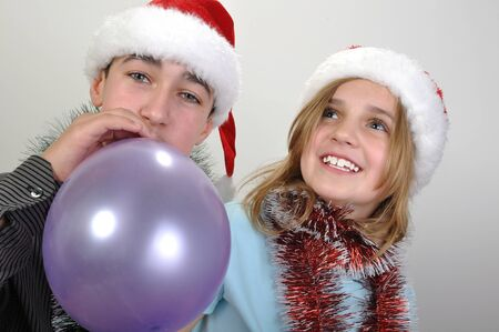 kidding: children with Santa hats  having fun  and blowing balloons Stock Photo