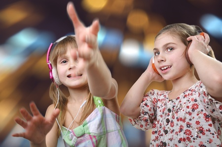 twocheerful  young girls with headphones against bright background photo