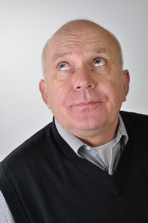 Studio portrait of bald elderly man looking up with funny expression  photo