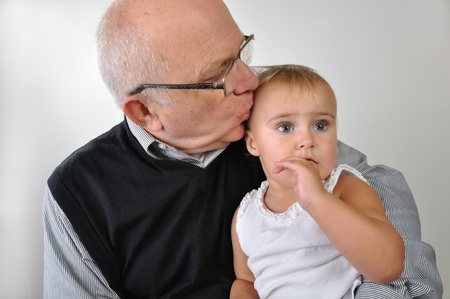 Cute baby with finger in her mouse sitting on grandfather's lap Standard-Bild