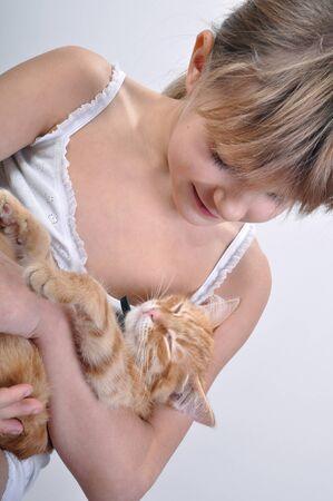 trustful: Trustful red kitten asleep in girls arms.
