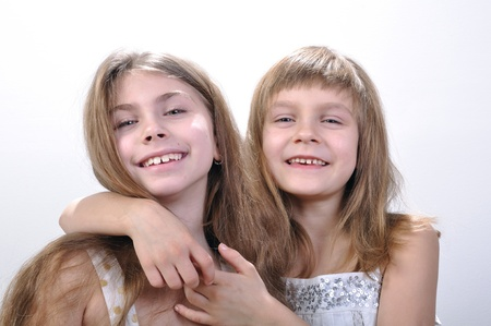 Studio portrait of two laughing hugging girls