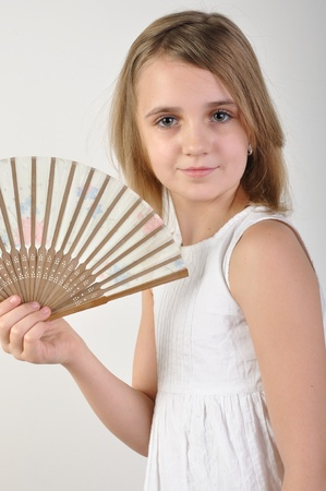 elementary age girl: portrait of a beautiful elementary age girl fanning herself