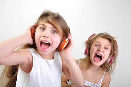two shouting young girls with headphones  Stock Photo - 12187491