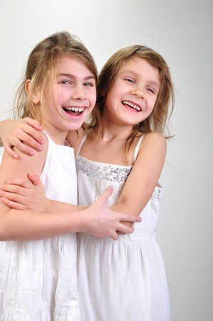 Studio portrait of two laughing hugging girls photo