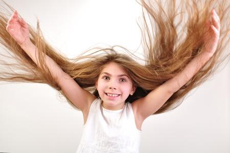 salto largo: hermosa niña feliz y sonriente con el pelo largo con viento Foto de archivo