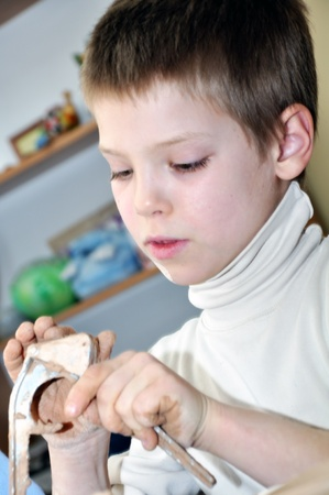 kid shaping clay in the pottery studio photo