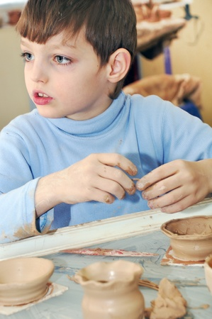 kid  shaping clay at pottery studio photo