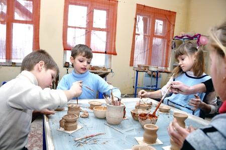 potters wheel: group of   children shaping clay pots and vases in pottery studio school  Editorial