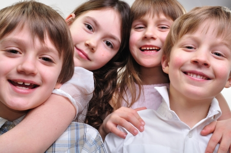 group of happy smiling children friends hugging and playing together