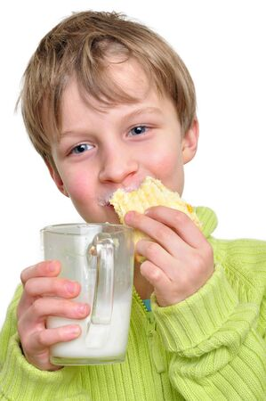 doughnut: portrait of an elementary age boy eating cake and drinking milk Stock Photo