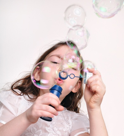 blow out: Little girl playing and blowing bubbles with bubble wand  Stock Photo