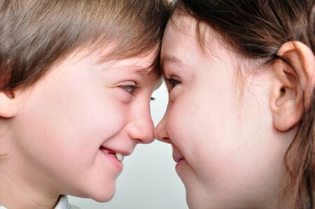 touching noses: close-up portrait of playful boy and girl