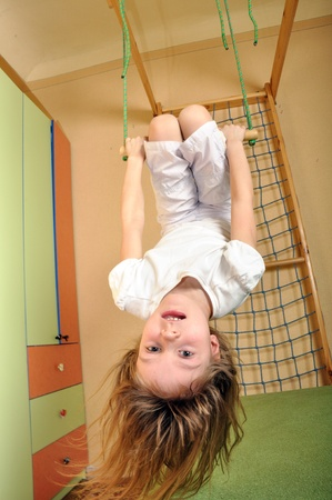 little girl doing sports and hanging down at gym