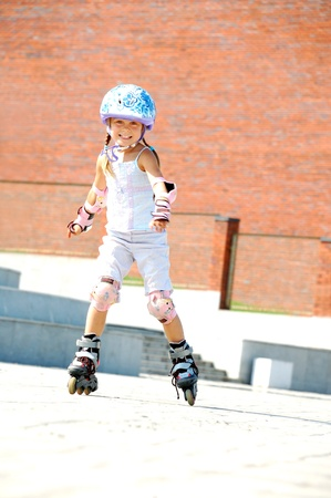 inline: rollerblading  smiling 5 year old girl  going on her in-line skates  Stock Photo