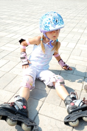 5 year old girl sitting in rollablade skates after fall photo
