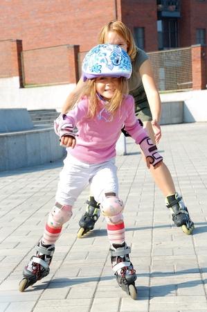 再生都市公園家族と一緒にローラー スケートで rolleblading 母は彼女の娘をキャッチしよう 写真素材