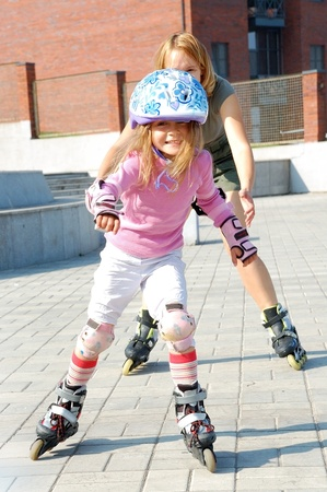 skate park: City park family playing and  rolleblading on roller skates together  Mother trying to catch her daughter   Stock Photo
