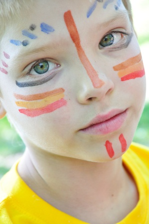 outdoor portrait of a child with paited face photo