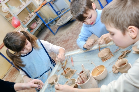 craft work: group of children shaping clay at the pottery studio