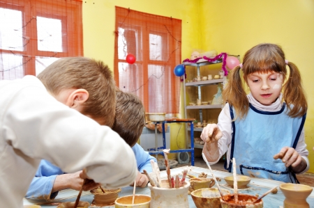 young children decorating tgier handmade clay pottery  photo