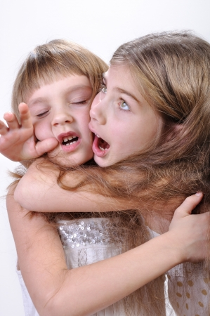 Studio portrait of two laughing hugging making faces girls photo