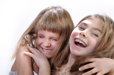 Studio portrait of two laughing hugging girls Stock Photo - 14726247