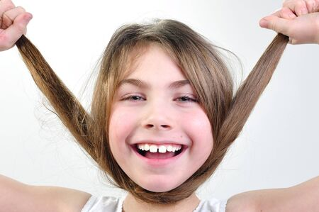 close-up portrait of a funny little girl playing with her hair photo
